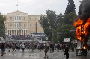 Una columna de anuncios de la municipalidad arde frente al parlamento griego (al fondo) durante enfrentamientos entre manifestantes y policías el miércoles 29 de junio de 2011 en la plaza Syntagma en Atenas. Los legisladores aprobaron un proyecto de ley crucial con medidas de austeridad para impedir que Grecia se declarara en julio en moratoria. (AP foto/Thanassis Stavrakis)